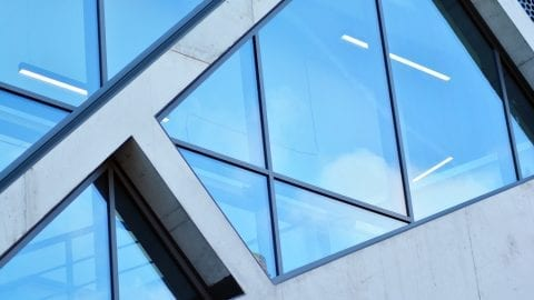 Abstract image of looking up at modern glass and concrete building